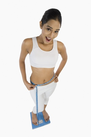 Woman on a weight scale and measuring her waist Stock Photo - 10125905