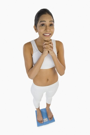 Woman measuring her weight on a weight scale Stock Photo - 10125896