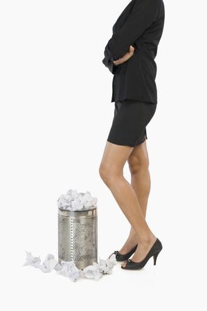 wastepaper basket: Imprenditrice in piedi davanti a un cestino della carta straccia LANG_EVOIMAGES