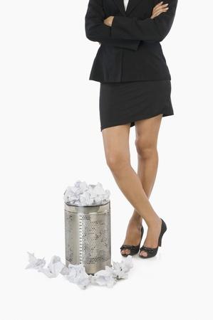wastepaper basket: Businesswoman in piedi davanti a un cestino della carta straccia