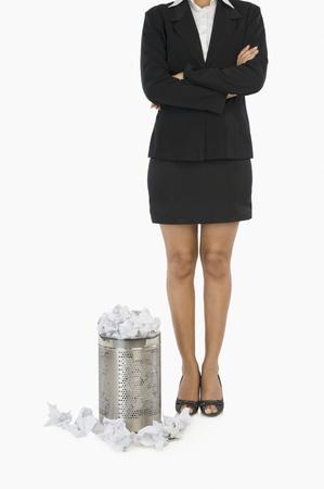 wastepaper basket: Imprenditrice in piedi davanti a un cestino per la carta