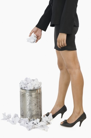 Businesswoman throwing crumpled paper into a wastepaper basket Stock Photo - 10125682