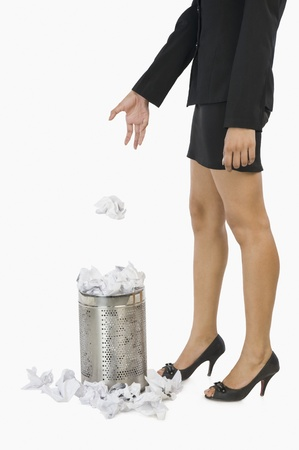 Businesswoman throwing crumpled paper into a wastepaper basket Stock Photo - 10124052