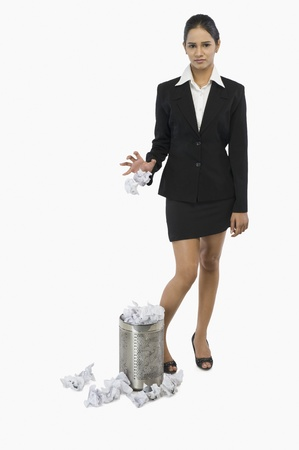 Businesswoman throwing crumpled paper into a wastepaper basket Stock Photo - 10125915