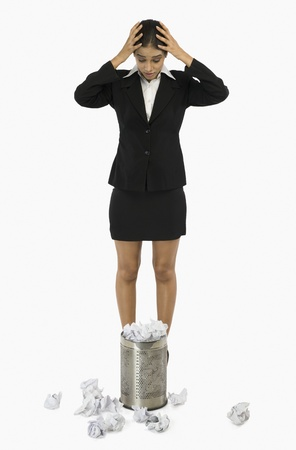 wastepaper basket: Businesswoman standing in front of a wastepaper basket and holding her head