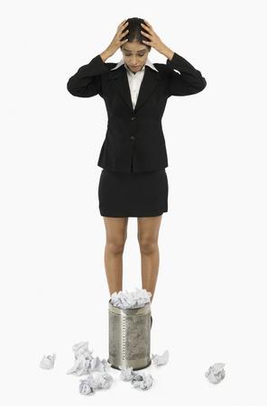 wastepaper basket: Imprenditrice in piedi davanti a un cestino della carta straccia e tenendo la testa