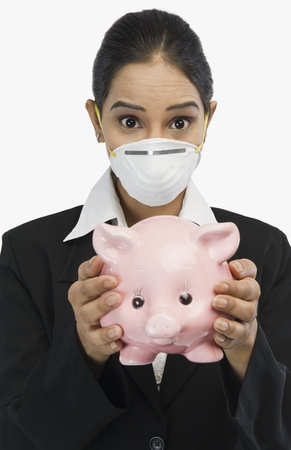 Businesswoman wearing an H1N1 mask and holding a piggy bank Stock Photo - 10125281