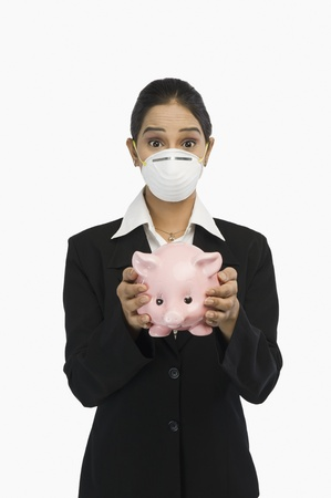 current events: Businesswoman wearing an H1N1 mask and holding a piggy bank LANG_EVOIMAGES