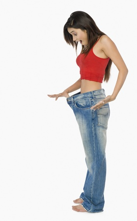 Woman pulling jeans from waistline to show weight loss and looking shocked Stock Photo - 10125597