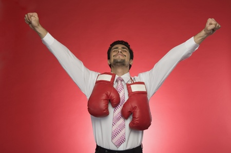 clenching: Businessman with boxing gloves clenching his fists
