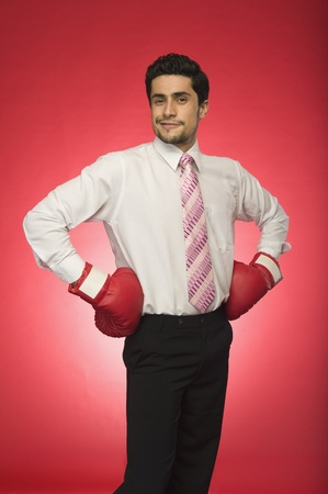 Portrait of a businessman wearing boxing gloves and standing with arms akimbo Stock Photo - 10167525