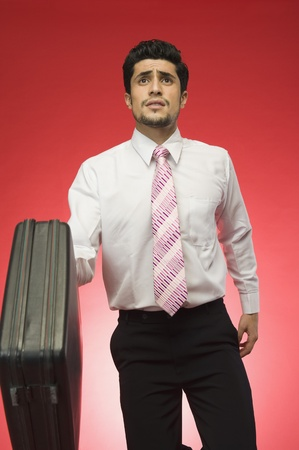 getting late: Businessman holding a briefcase and looking worried