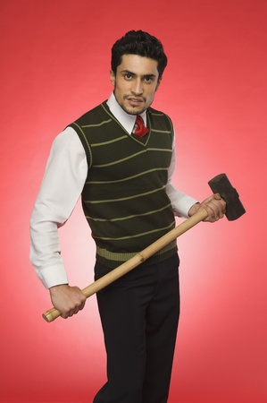 displeased businessman: Portrait of a businessman holding a sledgehammer