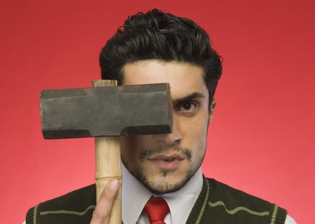 Portrait of a businessman holding a sledgehammer in front of his face Stock Photo - 10168052