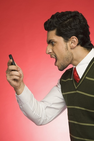 displeased businessman: Businessman shouting on a mobile phone