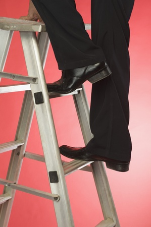 Businessman moving up a step ladder Stock Photo - 10167470