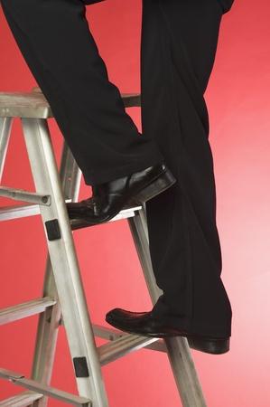 Businessman moving up a step ladder