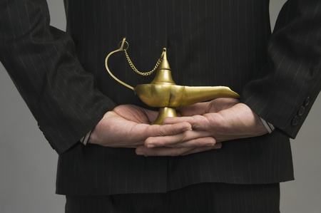 businessman standing: Mid section view of a businessman holding a magic lamp