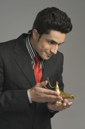 Close-up of a businessman holding a magic lamp Stock Photo - 10168026