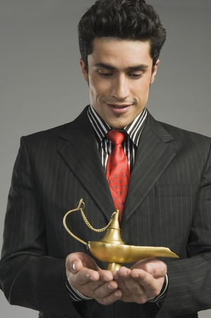lampe magique: Gros plan d'un homme d'affaires tenant une lampe magique