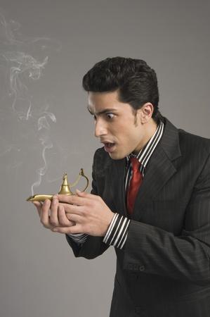 lampe magique: Close-up d'un homme d'affaires se gratter une lampe magique LANG_EVOIMAGES
