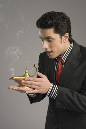 Close-up of a businessman scratching a magic lamp Stock Photo - 10168045
