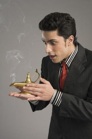lamp: Close-up of a businessman scratching a magic lamp
