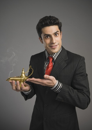 Portrait of a businessman holding a magic lamp Stock Photo - 10167506