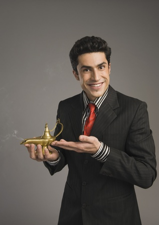 Portrait of a businessman holding a magic lamp Stock Photo - 10167488