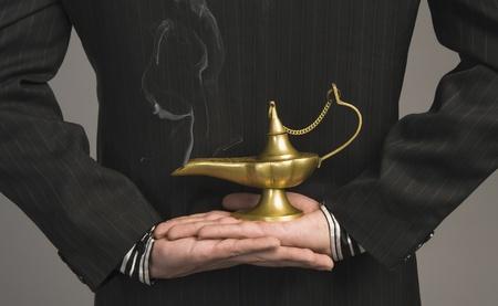 lampada magica: Vista di sezione met� di un imprenditore che tiene in mano una lampada magica LANG_EVOIMAGES