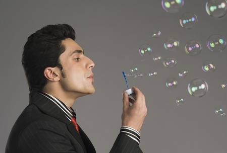 Businessman blowing bubbles