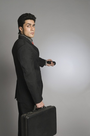 Businessman holding a briefcase and a flashlight Stock Photo - 10167590