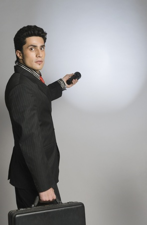 Businessman holding a briefcase and a flashlight