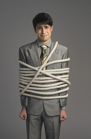 tied up: Portrait of a businessman tied up with ropes LANG_EVOIMAGES
