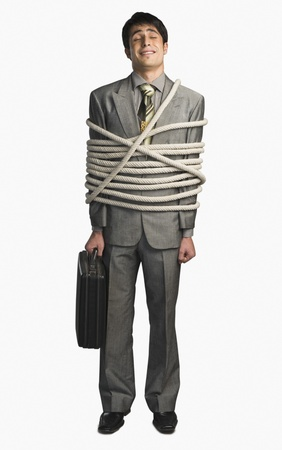 Businessman tied up with ropes and holding a briefcase Stock Photo - 10167109