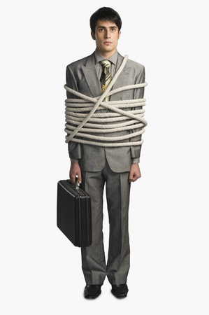 Businessman tied up with ropes and holding a briefcase