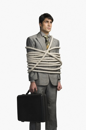 Businessman tied up with ropes and holding a briefcase Stock Photo - 10168609