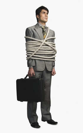 Businessman tied up with ropes and holding a briefcase Stock Photo - 10168744
