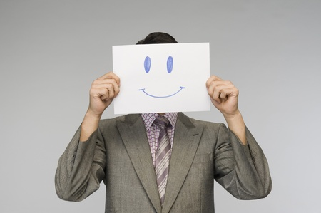 covering: Businessman holding a smiley face paper in front of his face LANG_EVOIMAGES