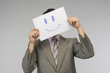 彼の顔の前でスマイリーの顔の紙を保持している実業家