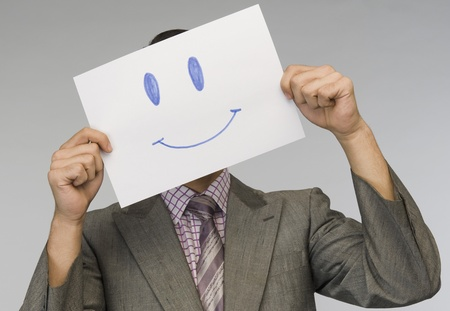 disguises: Businessman holding a smiley face paper in front of his face LANG_EVOIMAGES