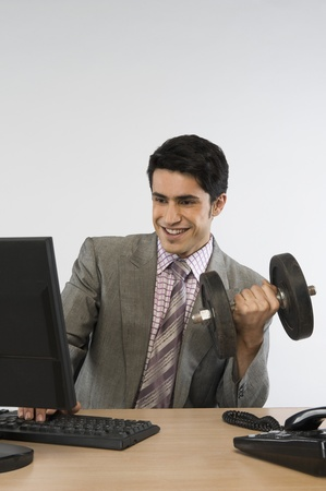 Businessman exercising with dumbbells and working on a computer Stock Photo