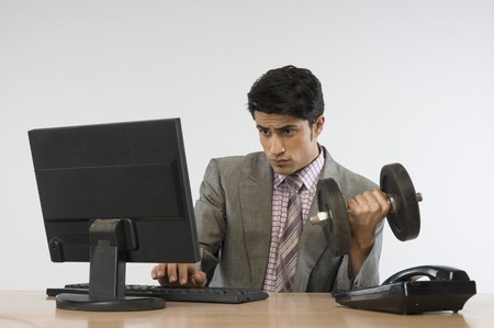 front desk: Businessman exercising with dumbbells and working on a computer LANG_EVOIMAGES