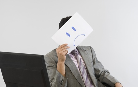 Businessman holding a smiley face paper in front of his face Stock Photo - 10167492