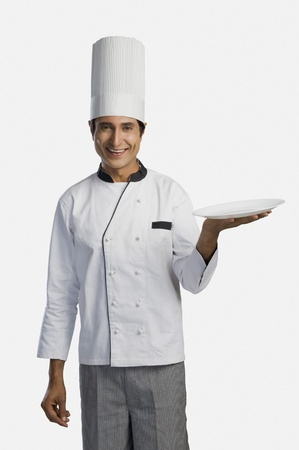 Portrait of a chef holding a plate and smiling Stock Photo - 10168643