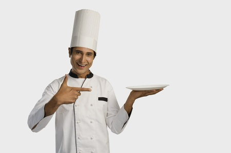 chefs whites: Portrait of a chef holding a plate and smiling