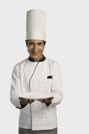 Portrait of a chef holding a plate and smiling Stock Photo - 10168646