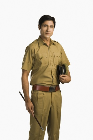 a police officer: Portrait of a police officer holding a nightstick and a cap