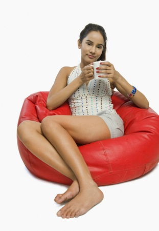 Woman sitting on a bean bag with a cup of coffee Stock Photo - 10167340