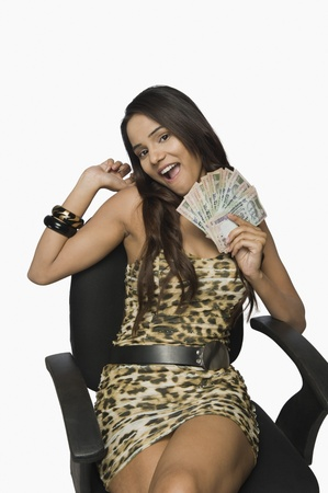 Woman holding currency notes and smiling Stock Photo - 10167346